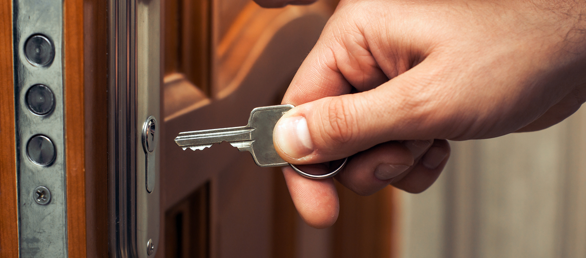 Hand putting a key in a door keyhole